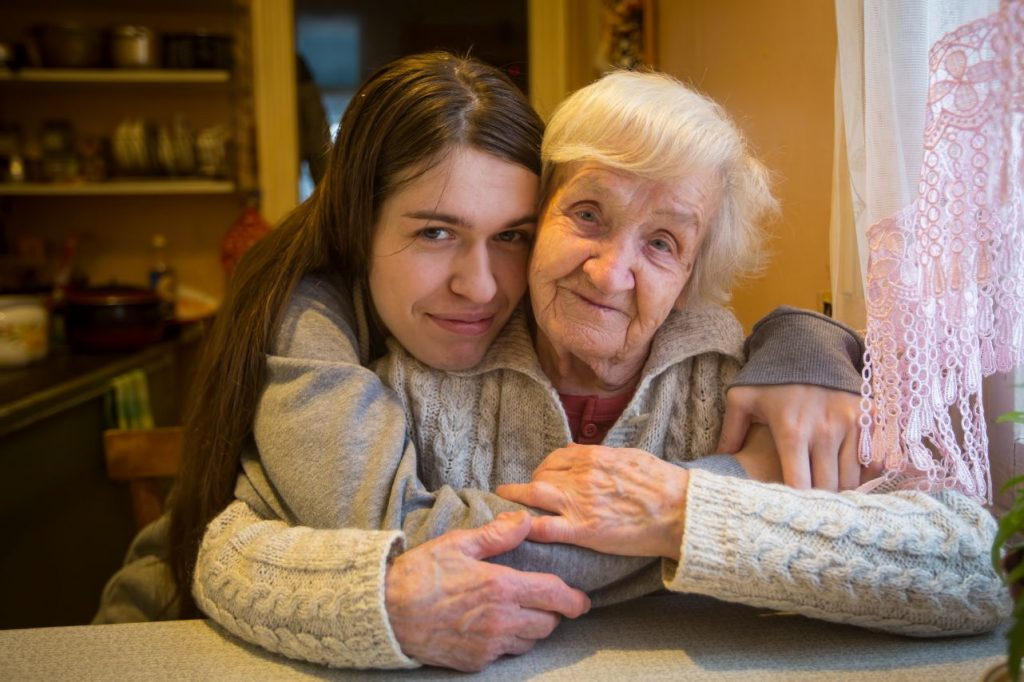 Older woman being hugged by younger woman