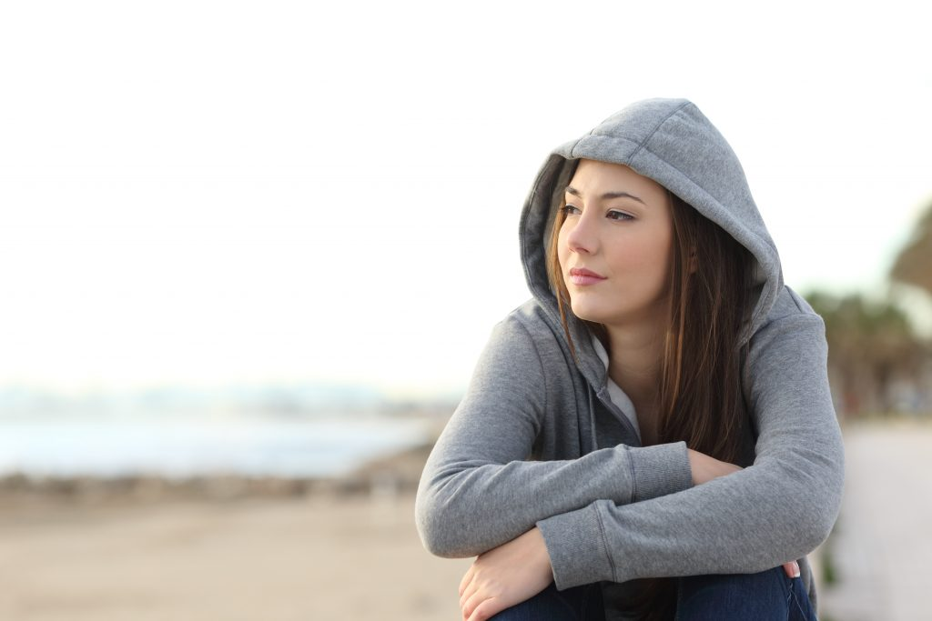 woman sitting at beach looking into distance